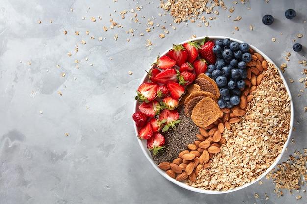 Graines de granola, flocons d'avoine, baies mûres et noix dans une assiette