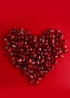 Graines de grenade rubis juteuses en forme de coeur isolées sur fond rouge, grenat d'amour, concept de la saint-valentin
