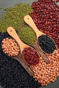 Graines de haricots (haricots noirs, haricots rouges, arachides et haricots mungo) utiles pour la santé dans des cuillères en bois.