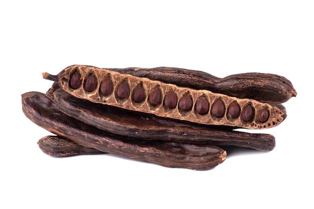 Graines de kerob isolées sur fond blanc. cacao végétarien