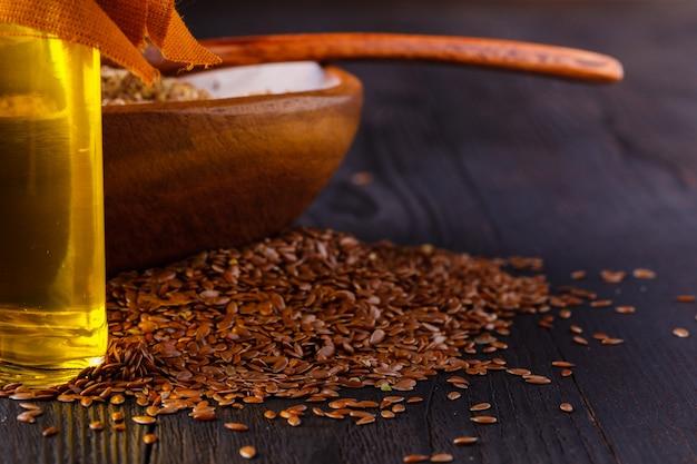 Graines de lin brun dans l'huile de lin spoonnd dans une bouteille en verre sur bois blanc. l'huile de lin est riche en acides gras oméga-3