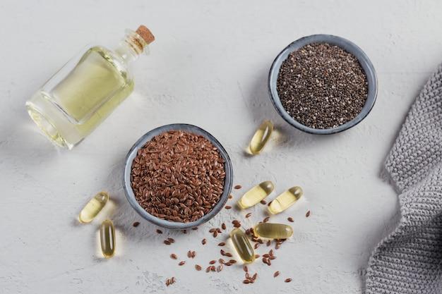 Graines de lin brun ou graines de lin et chia dans un petit bol et capsules de gélatine avec de l'huile oméga sur fond gris clair. vue de dessus