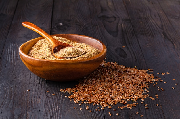 Graines de lin brun sur l'huile de lin spoonnd dans une cruche en verre sur une table en bois. l'huile de lin est riche en acides gras oméga-3.