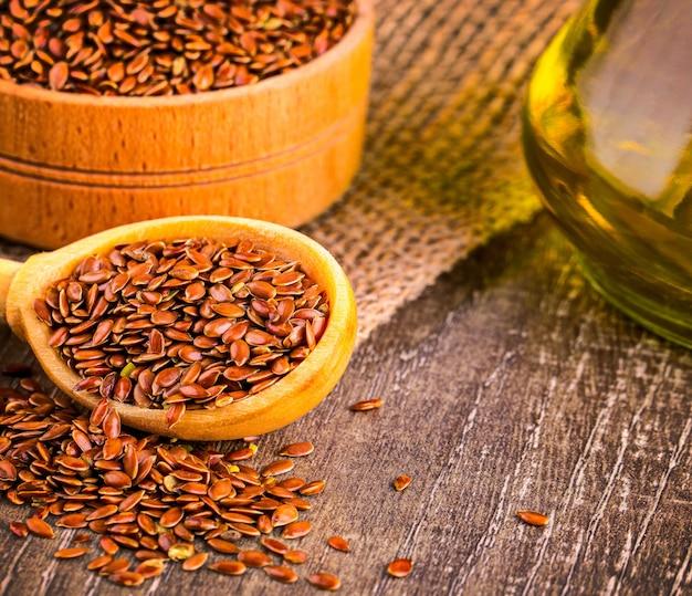 Graines de lin brun et huile de lin sur une surface en bois