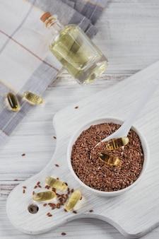 Graines de lin brun ou de lin dans un petit bol et capsules de gélatine avec de l'huile oméga sur bois blanc. vue de dessus
