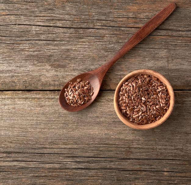Graines de lin brun sec dans une cuillère en bois brun sur une table en bois gris de vieilles planches