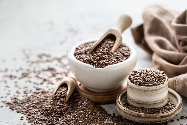Graines de lin dans un bol en céramique avec une cuillère en bois. aliments sains biologiques.