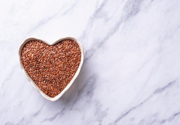 Graines de lin dans un bol en forme de coeur