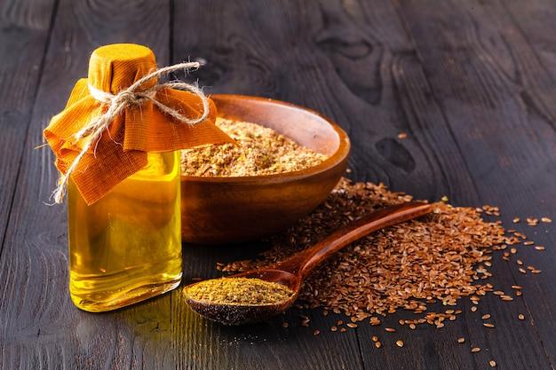 Graines de lin dans un bol et huile de lin dans une bouteille en verre sur bois