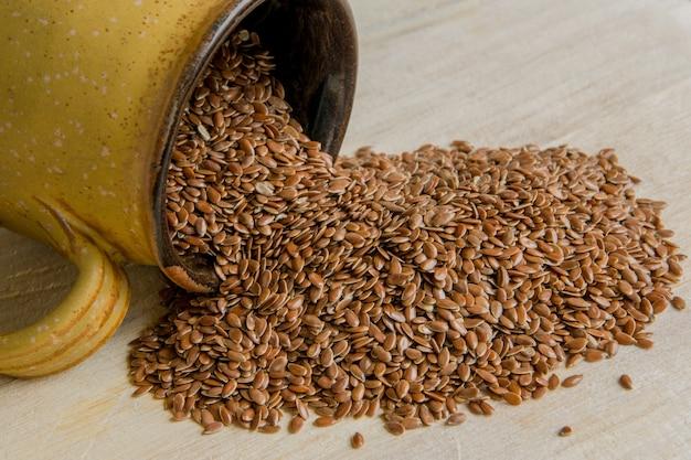 Graines de lin dans une tasse sur fond de bois concept de nutrition saine