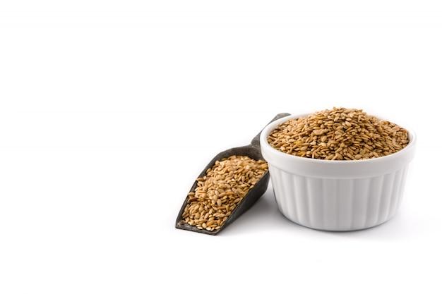 Graines de lin doré dans un bol blanc copie espace isolé