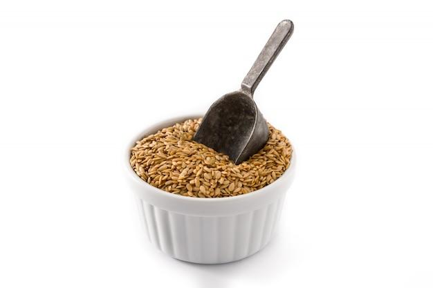 Graines de lin doré dans un bol blanc isolé.