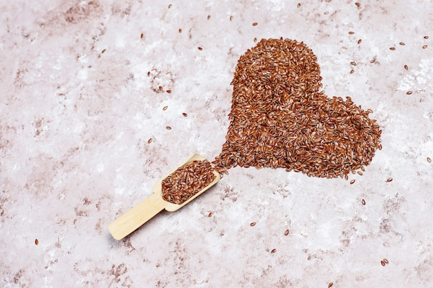 Graines de lin en forme de coeur sur fond de béton avec espace pour copie, vue de dessus
