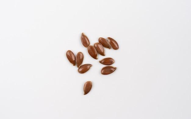 Graines de lin isolées sur fond blanc vue de dessus macro shoot de graines de lin lin sèches étalées sur