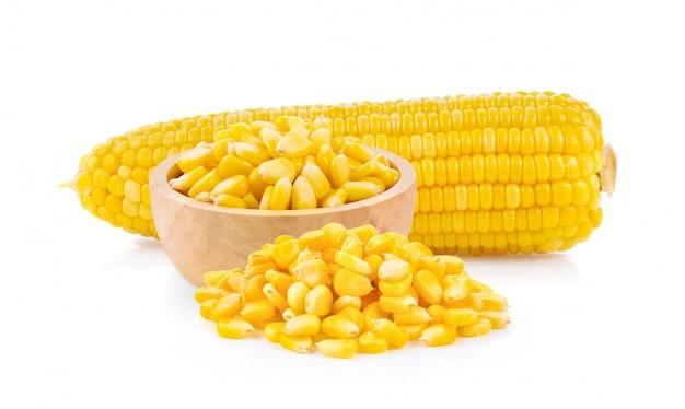Graines de maïs dans un bol en bois isolé sur le blanc