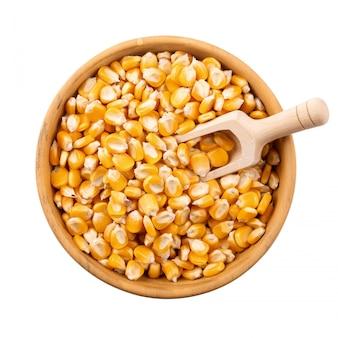 Graines de maïs dans un bol en bois isolé sur fond blanc