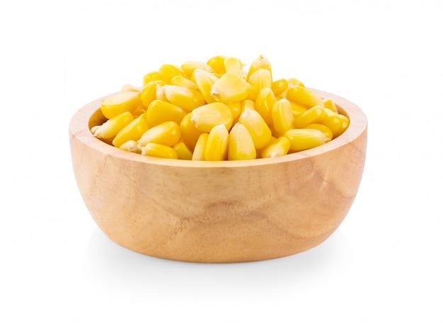 Graines de maïs dans un bol en bois isolé