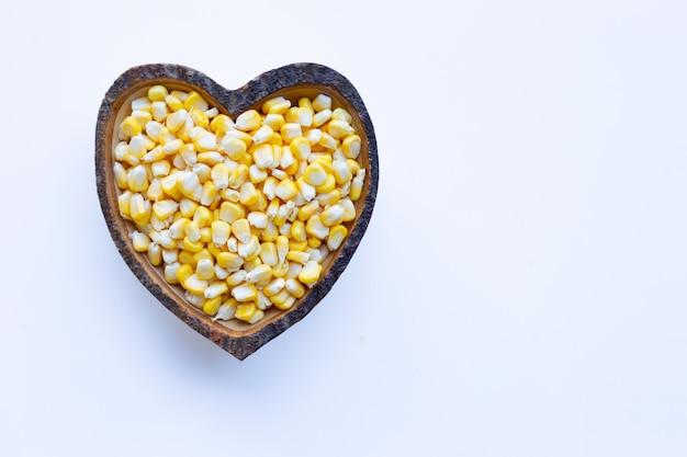 Graines de maïs dans un plat en forme de coeur en bois sur fond blanc