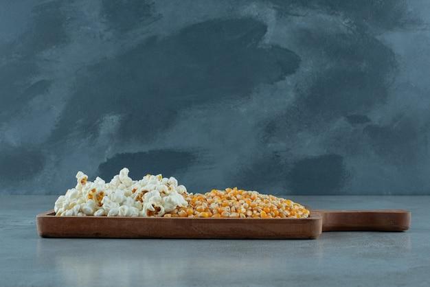 Graines de maïs et pop-corn sur fond bleu. photo de haute qualité