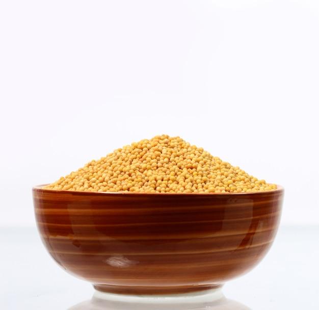 Graines de moutarde jaune dans un bol isolé sur blanc