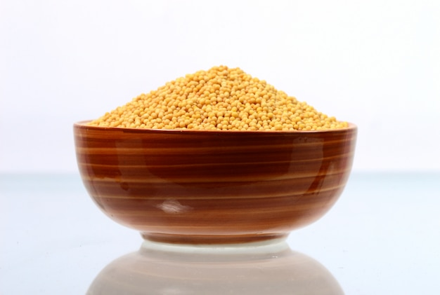 Graines de moutarde jaune dans un bol isolé sur fond blanc