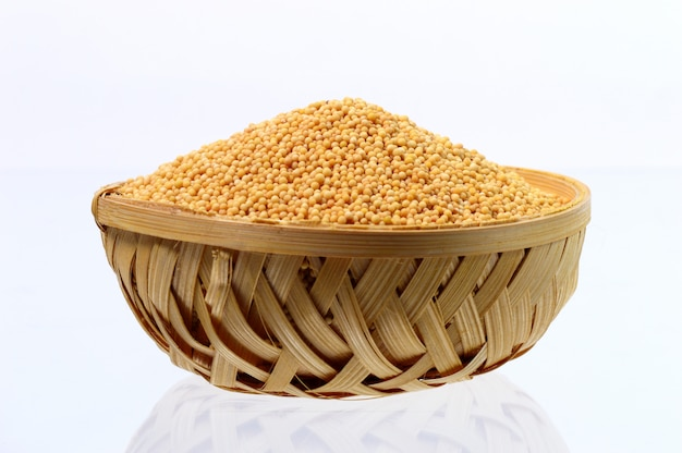 Graines de moutarde jaune dans un panier en bois isolé sur fond blanc