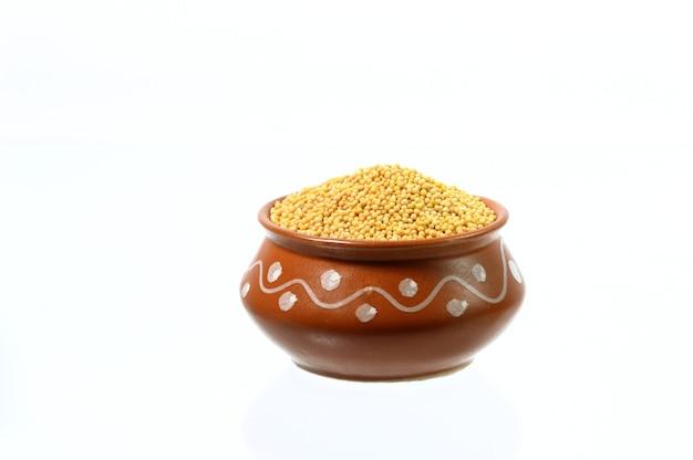 Graines de moutarde jaune en pot d'argile isolated on white
