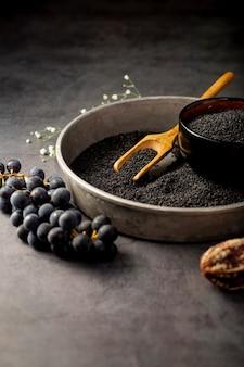 Graines de pavot dans une assiette métallique et raisins sur fond gris