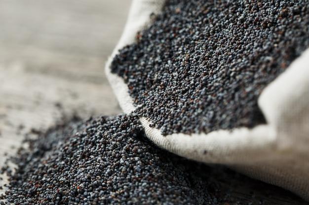 Graines de pavot dans un sac en jute. les graines savoureuses et utiles riches en protéines et en huiles.