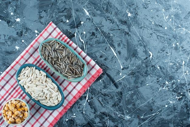 Graines de pois chiche et de tournesol sur des bols sur le torchon, sur la table bleue.