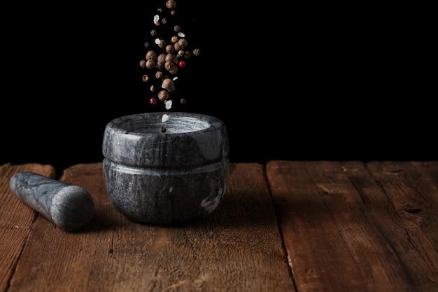 Les graines de poivre tombent dans le mortier.