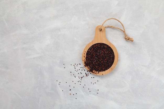 Graines de quinoa noir ou ragi dans une planche de service en bois sur fond clair vue de dessus