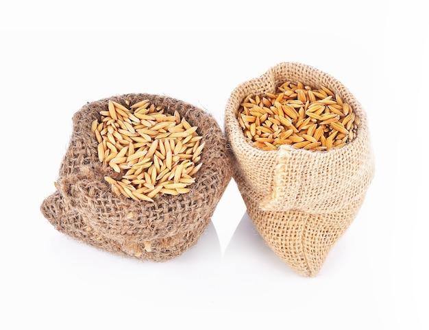 Graines de riz paddy en sac sur blanc