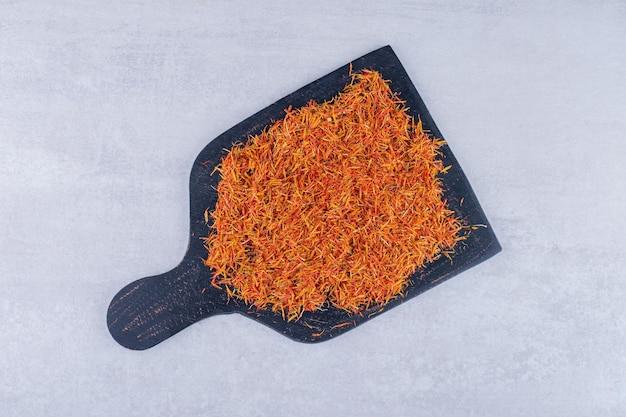 Graines de safran sur un plateau en bois noir. photo de haute qualité