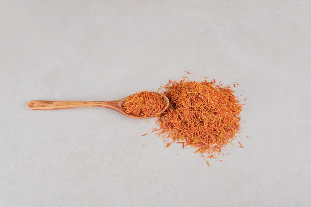 Graines de safran rouge dans une cuillère en bois.