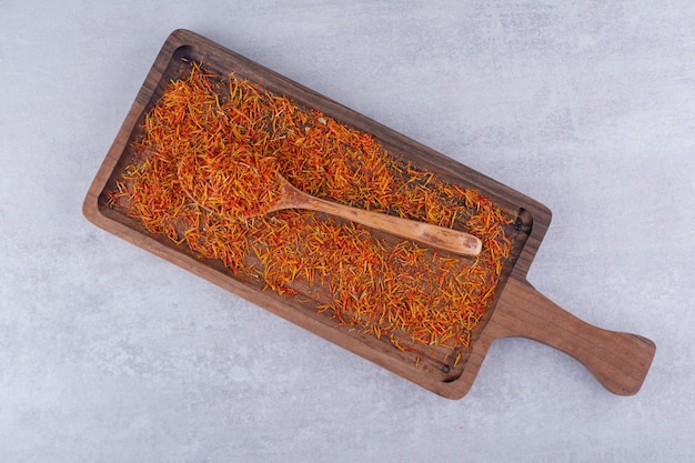 Graines de safran rouges isolées sur un plateau en bois. photo de haute qualité