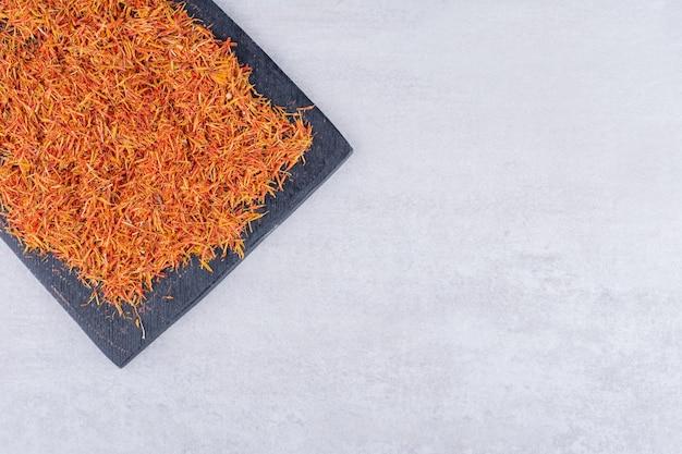 Graines de safran rouges sur un plateau noir