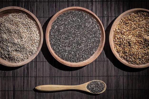 Graines de sésame, chia et lin dans des plats en bois, cuillère en bois avec chia sur socle en bois