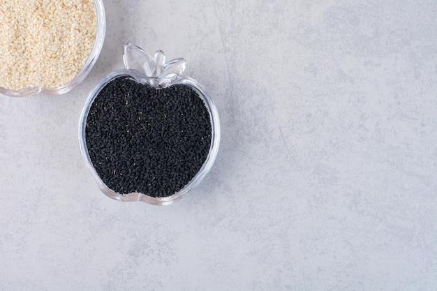 Graines de sésame et de cumin noir dans des coupes en verre.