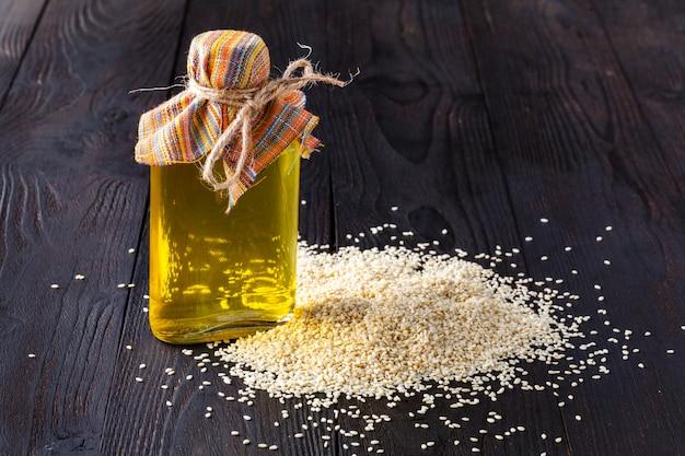 Graines de sésame et huile sur table en bois