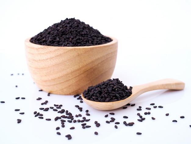Graines de sésame noir dans une cuillère en bois isolé sur une surface blanche.