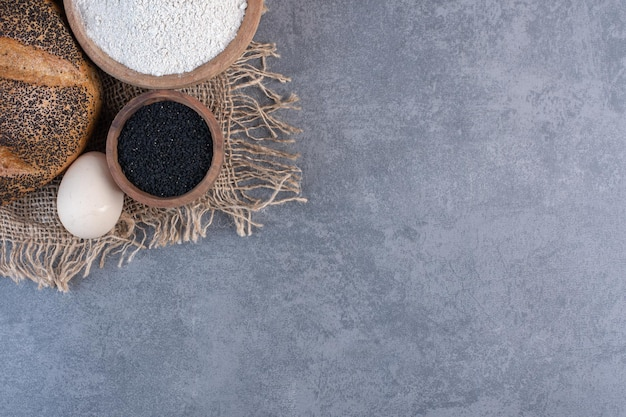 Graines de sésame noires, farine, œuf et pain enrobé de sésame sur fond de marbre. photo de haute qualité