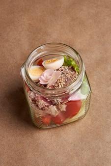 Graines de sésame avec thon frit et salade verte et œufs de caille dans un bocal en verre.