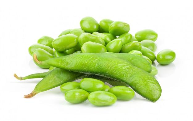 Graines de soja vert sur mur blanc.