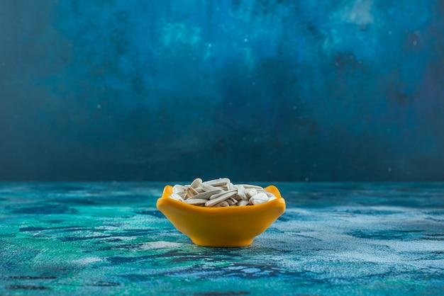 Graines de tournesol biologiques blanches dans un bol sur bleu.
