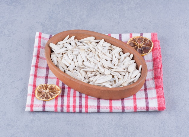 Graines de tournesol blanches dans un bol à côté de citron séché sur un torchon sur marbre.
