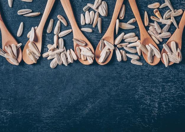 Graines de tournesol blanches dans une cuillère et autour sur un fond noir. vue de dessus. espace pour le texte