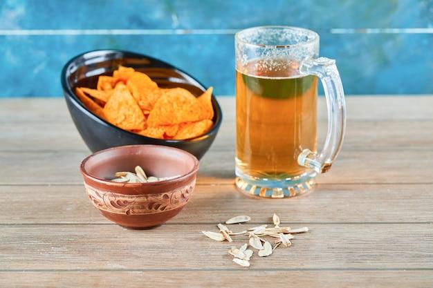Graines de tournesol, un bol de chips et un verre de bière sur une table en bois.