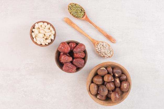 Graines de tournesol et de citrouille et bols de noix sur une surface blanche.