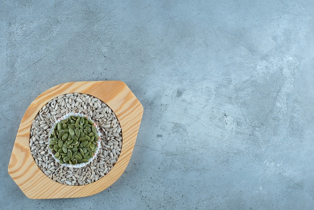 Graines de tournesol et de citrouille verte sur un plateau en bois. photo de haute qualité